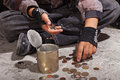 Beggar child counting coins sitting on damaged concrete floor closeup hands Royalty Free Stock Image