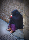 Beggar woman sitting on the street holding a cup begging for money Stock Photos