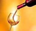 Begin filling red wine in the glass tilted on golden background Stock Photography