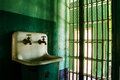Behind the bars of a local prison ther is a dirty sink that could use some cleaning Royalty Free Stock Photos