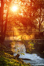Behind trees sun rising over a small village water fall with a fog and Stock Image