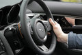 Behind the wheel in jaguar close up of a man s hand holding steering Royalty Free Stock Photo
