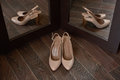 Beige bride shoes on a wooden floor and two reflection in the mirror Royalty Free Stock Photo