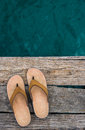 Beige flip-flop sandals on edge of wooden dock over water Royalty Free Stock Photo