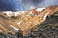 The beige rhyolite mountains with snow orange and in hollows national park landmannalaugar in iceland pieces of gray and black Royalty Free Stock Image