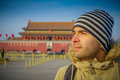 BEIJING, CHINA - 29 JANUARY, 2017: Hispanic tourist on Tianmen square looking around, famous forbidden city building in Royalty Free Stock Photo