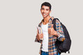 Being a student is cool handsome young afro american holding books and stretching out hand with thumb up while standing against Royalty Free Stock Image