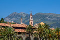 Belfry among houses and palms in menton france catholic church bell tower mountain on background under blue sky Stock Photos