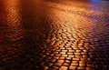 Belgian block pavement of the night city wet with light spots Royalty Free Stock Photography