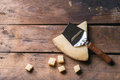 Belgian cheese big piece and little cubes of with knife over wooden background top view Stock Images
