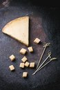 Belgian cheese big piece and little cubes of over black background top view Royalty Free Stock Photo