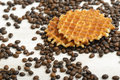 Belgian Waffle biscuit and coffee beans scattered on light surface Royalty Free Stock Photo