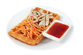 Belgian waffle with chicken and carrot salad fast food on the plate the a of grated slices of breast a bowl of red sauce isolated Royalty Free Stock Photography