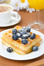 Belgian waffles with blueberries coffee and orange juice for br breakfast closeup vertical Royalty Free Stock Photo