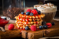 Belgian waffles with fresh berries and coffee on cutting board on rustic wooden background Royalty Free Stock Image