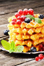 Belgian waffles with fresh berries on wooden table Royalty Free Stock Images