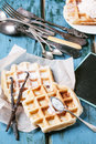 Belgian waffles fresh served with vanilla sticks and vintage cutlery over blue wooden table Royalty Free Stock Photo