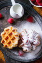Belgian waffles with raspberries and sugar powder served jug of milk on vintage metal tray textile napkin over rusty Royalty Free Stock Images