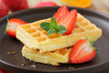 Belgian waffles stack of delicious freshly baked with fresh strawberries and liquid honey Royalty Free Stock Photo