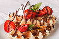 Belgian waffles with strawberries, whipped cream and chocolate m Royalty Free Stock Photo