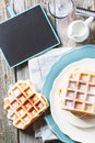 Belgian waffles top view on plates with fresh served with empty black chalkboard over old wooden table see series Stock Photography