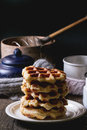 Belgian waffles white plate with homemade with two vintage cup of tea at background over old wooden table dark rustic style Royalty Free Stock Photo