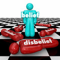 Belief vs disbelief one confident person with faith stands doubt word on a standing as winner or victor on a chess board while Royalty Free Stock Photography