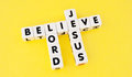 Believe in lord jesus text and uppercase black letters on white cubes arranged crossword style with common letters l and e yellow Stock Photography