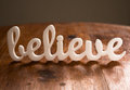 Believe on wooden table with reflection Stock Photo