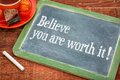 Believe you are worth it motivational advice on a slate blackboard with chalk and cup of tea Royalty Free Stock Images