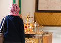 Believer woman praying christian russian orthodox pilgrim prays in front of golden decorated crucifix and burning candles in old Stock Images