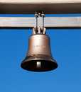 Bell a bronze on blue sky hanging on a beam Royalty Free Stock Photo