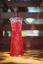 Red soda iced water in a glass with blur wooden background, summer drinking , cooling fresh Royalty Free Stock Photo