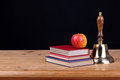 Bell on a school desk black background with books and apple against add your own text Royalty Free Stock Images