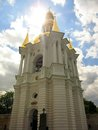 Bell tower of Kiev-Pechersk Lavra with bright sun on blue sky with white clouds. Royalty Free Stock Photo