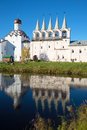 The bell tower of the Tikhvin assumption monastery and its reflection in the monastery pond, evening. Tikhvin, Russia Royalty Free Stock Photo