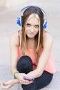 Bella donna casuale che ascolta la musica con le cuffie ed il ph Immagine Stock