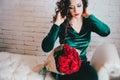 Bella donna in un vestito verde e nelle scarpe rosse con le rose rosse Immagini Stock Libere da Diritti