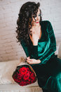 Bella donna in un vestito verde e nelle scarpe rosse con le rose rosse Fotografie Stock