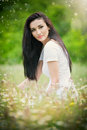 Bella giovane donna nel giacimento di fiori selvaggi ritratto della ragazza castana attraente con capelli lunghi che si rilassano Fotografia Stock
