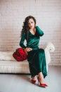 Belle femme dans une robe verte et des chaussures rouges avec les roses rouges Photos libres de droits
