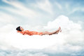 Belle fille dormant sur un nuage blanc Photos stock