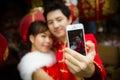 Belle photo de selfie de couples par le smartphone avec le chinois de papier rouge Image libre de droits
