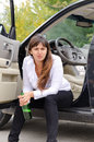 Belligerent drunk woman sitting in the open door of her car on the sill glaring at the camera as she clutches her bottle of Royalty Free Stock Photos