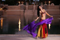 Belly dancer in red costume dances with purple veil a beautiful brunette wearing a dancing a silk she is at an upscale Royalty Free Stock Photos
