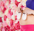 Belly of a pregnant woman pregnancy maternity and health concept with pink baby booties Royalty Free Stock Photos