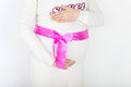 Belly of pregnant woman in white with pink ribbon on background Royalty Free Stock Photos