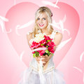 Beloved flower girl be my valentine smiling offering over bouquet of fresh flowers in a on pink heart studio backdrop Stock Photos