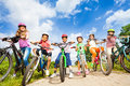 Below angle view of kids in helmets with bikes who hold their and stand on path Stock Image