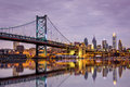 Ben franklin bridge and philadelphia skyline reflected in the delaware river under a purple twilight Royalty Free Stock Image